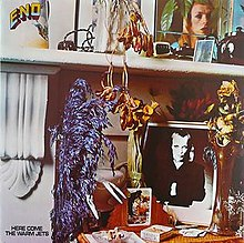 """A close up photo of a mantle with a desk below it. Items on the mantle include a color photo of Brian Eno, a kettle and flowers. Items on the desk below are a black-and-white photo of Eno, flowers, playing cards and cigarettes. In the top left corner of the album cover """"Eno"""" is written. At the bottom left corner of the album, """"Here Come the Warm Jets"""" is written."""
